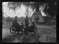 Will Connell (possibly) and another man next to parked motorcycles in front of a rural church, circa 1920
