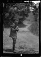 Will Connell (possibly) in rural setting standing next to a dirt road, circa 1920