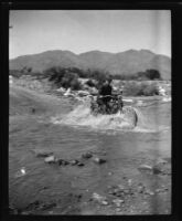 Man crossing a stream on a motorcycle, circa 1920