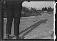 Legs of man standing on a narrow paved road, circa 1920