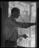 Unidentified man looking out a screen door, circa 1920