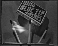 Three matches burning beneath a box of Ohio Blue Tip Matches, 1925-1939