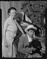 Will Harrison and his wife Evelyn Harrison (probably) in a comic pose with another man behind the curtain holding a rifle, Santa Fe (probably), 1930-1948