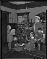Children receive Christmas gifts from Santa at the Native Daughters of the Golden West holiday party, Los Angeles, 1935