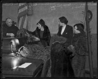 Barbara Woodling, Terrys Gambord, and Mrs. Alemeda Finley display furs before Judge William R. McKay in courtroom, Los Angeles, 1936