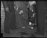 Pedro Garong speaks with Officer R. W. Clark after being shot by gang members in Ferguson Alley, Chinatown, Los Angeles, 1936