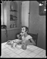 An unidentified girl enjoys a meal, Los Angeles, 1936