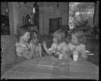 Three unidentified girls feed a dog an avocado, Los Angeles County, 1935