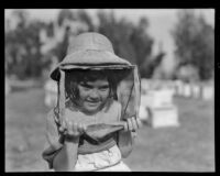 Young girl visits a bee farm, Los Angeles County, 1935