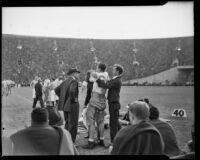 Howard Jones coaches Trojan Al Krueger before he enters the field against Notre Dame, Los Angeles, 1938