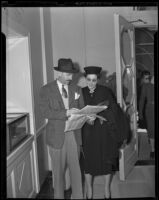 Man and woman reviewing horse race literature at Santa Anita Park, Arcadia, 1938 or 1939