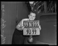 Allyne Pyle holds a license plate for 1938 under the model for the new 1939 license plate, Los Angeles, 1938