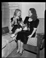 Mrs. Russell Smith and Lynn Helm play with toys while modeling winter fashion, Los Angeles, 1938
