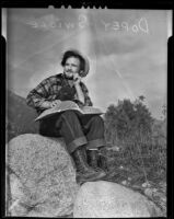 Travelling wrestler Dopey Swigle sits atop a boulder in Santa Anita Canyon and teaches himself to read, Los Angeles, 1938