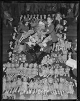 Santa Claus surrounded by baby dolls and two little girls, Los Angeles, 1938