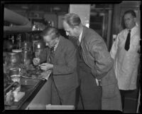 Dr. Frank R. Webb inspects remains from murder site as Ray Pinker observes, Los Angeles, 1938