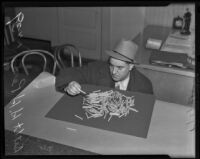 Detective Lieutenant Henry H. Perry examines confiscated drugs, Los Angeles, 1939