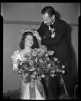 Lathrop K. Leishman places a crown on the head of Tournament of Roses queen Barbara Dougall, Pasadena, 1938
