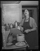 Singer Mariska Aldrich prepares food over a stove, Los Angeles, 1935