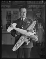 Captain Clem Peoples, Los Angeles County jailer, holds a model airplane, Los Angeles, 1920-1939