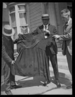 Three men hold a woman's garment, related to the investigation of the murder of Alberta Meadows by Clara Phillips, 1922-1923