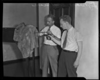 Ray Pinker and Robert Seares examine a bullet hole in a coat, Los Angeles, 1929-1939