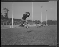 Pomona College football player practices catching at the first practice of the season, Pomona, 1933