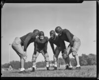 Four Pomona College football players on the field on the first day of practice, Pomona, 1933