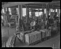 Interior view of the Roberti Brothers' furniture factory with stacks of lumber on carts, Los Angeles, circa 1920-1930