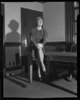 Shirley Ross, actress and singer, seated on a table in an office, 1933