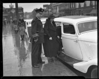 Police Chief James E. Davis and Gertrude Rounsavelle enter police car, Los Angeles, 1935