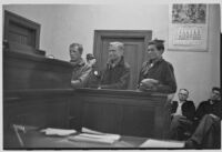 Night court at Lincoln Heights, with three young men at the judge's bench, Los Angeles, 1935