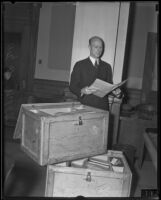 William H. Neblett, attorney, in court holding documents contained in 2 shipping boxes, Los Angeles, circa 1935