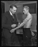 Dr. Clark D. Ryan gives a medical examination to Naval militia recruit Arthur Morriss, 1935