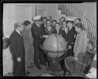 Navy officers provide instruction to militia recruits gathered around a globe, 1935