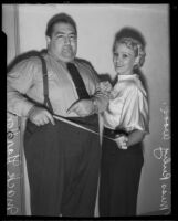 Mack Gordon, song writer, and Ruby Wood smile with satisfaction over his weight loss, Los Angeles, 1935