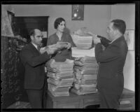 Ethel E. Lewis, R. P. Benton, and civic leader, David R. Faries pile petitions against the state personal income tax initiative, Los Angeles, 1935