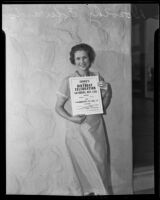Dorothy Edwards, 1933 Rose Queen, holds a sign announcing Covina's birthday celebration, Covina, 1935