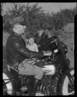 Motorcycle Officer Frank Conkey shows new radio receiver to Dave Harris and Jack Johnson, Los Angeles, 1935