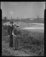 T. J. Hoyt and Dorothy Evans look towards the salt Lake tract, proposed pleasure harbor site, Redondo Beach, 1935