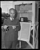 Floyd D. Young, meteorologist, standing outside beside a hydrograph, Pomona, 1935