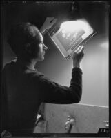 Photographer or technician holding an exposed and developed photographic sheet up to a light source, Los Angeles, 1935