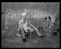 Boy Scout at camp event, wearing an apron and chef's hat, seated at a camp table, circa 1935