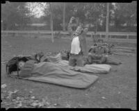 Boy Scouts with sleeping bags at a camping event in a park, circa 1935