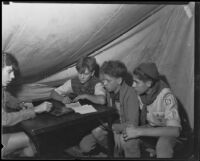 Boy Scouts in a tent at a camping event in a park, circa 1935