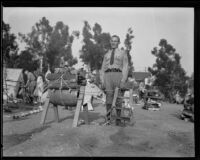 Boy Scout leader stands next to a sawhorse animal at a camping event in a park, circa 1935