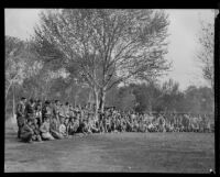 Boy Scouts grouped in a half circle at a camping event in a park, circa 1935