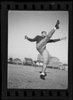 Bud Langley, USC football player, kicking a football, Los Angeles, 1935