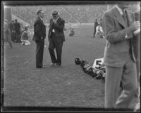 Stub Allison, assistant coach of the Golden Bears, talks with a man during a match with the USC Trojans at the Coliseum, Los Angeles, 1934