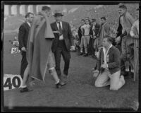 Stub Allison, assistant coach of the Golden Bears, approaches a player draped in a blanket as other players watch in the sideline at the Coliseum, Los Angeles, 1934
